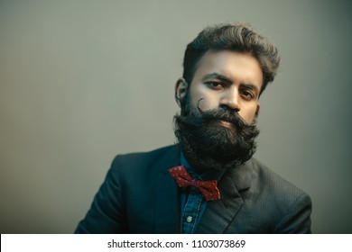 Portrait of young man posing with beard in suit