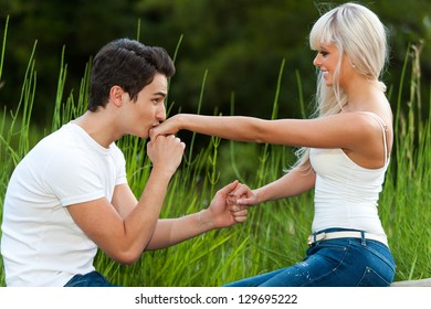 Portrait of young man proposing to girl with kiss on the hand.