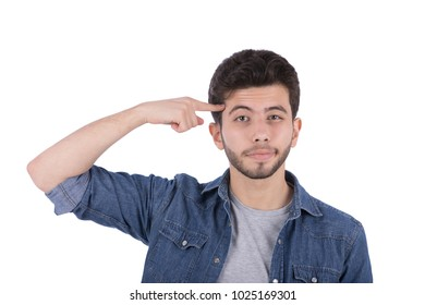 A portrait of a young man puts a finger on the head as he got a good idea with a weird face emotion, isolated on a white background.