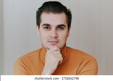 portrait of a young man. The man rests his chin on his hand and looks at the camera