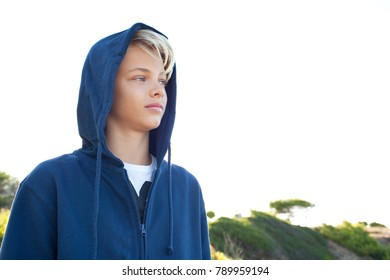 Portrait of a young man serene and contemplative against a sunny sky on holiday, wearing hood and sweatshirt keeping warm in park, outdoors. Teenager male relaxing calm and enjoying nature, exterior.