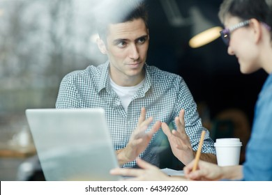 Portrait of young man sharing ideas with colleague during work meeting creative teams office