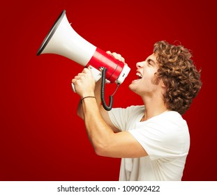 Portrait Of Young Man Shouting With A Megaphone Isolated On Red Background