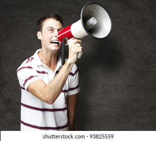 portrait of a young man shouting with a megaphone against a grunge wall
