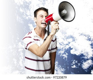 portrait of a young man shouting with a megaphone with a cloudy sky as a background