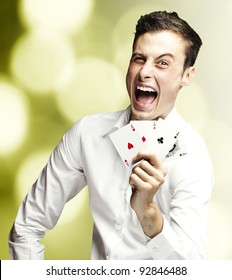 portrait of young man showing poker cards against a abstract background