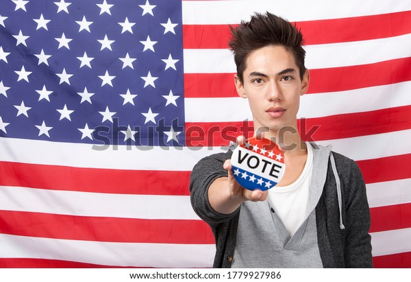 Portrait of young man showing vote badge standing against American flag