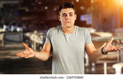 Portrait young man shrugging shoulders