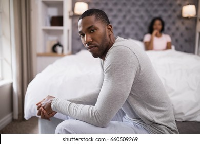 Portrait of young man siting while woman resting on bed at home