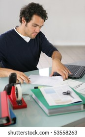 Portrait of a young man sitting at a desk with documents