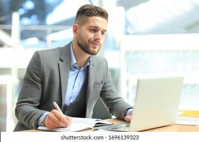 Porträt eines jungen Mannes, der an seinem Schreibtisch im Büro sitzt.