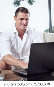 portrait of young man sitting with laptop in summer house environment