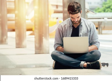 Portrait of young man sitting on the floor.Business man working with laptop.Happy young man working on laptop sitting at his working place outdoors.Successful business.