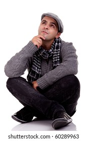 Portrait of a young man sitting on the floor, thinking and looking up, in autumn/winter clothes, isolated on white, Studio shot