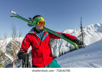 Portrait young man ski goggles holding ski in the mountains.