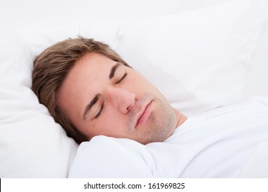 Portrait Of Young Man Sleeping In Bed