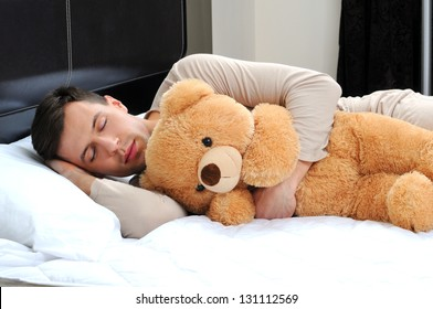 portrait of a young man sleeping on the bed embracing his soft toy