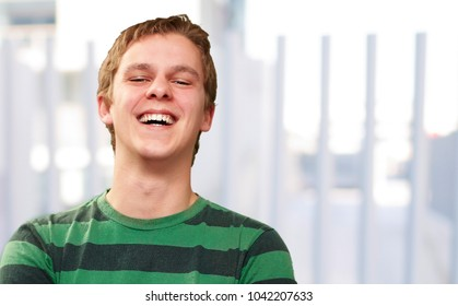 portrait of young man smiling against a fence