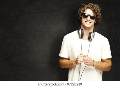 portrait of a young man smiling with headphones against a grunge wall