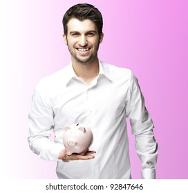 portrait of young man smiling and holding a piggy bank against a  pink background
