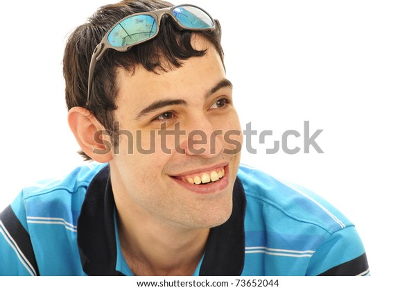 Portrait of a young man smiling with sunglasses on his head