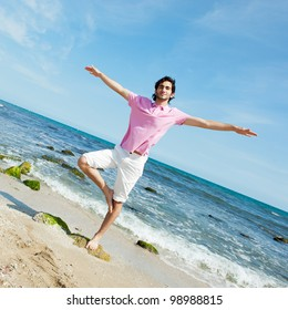 Portrait of young man standing carefree with outstretched arms on the beach. Copyspace