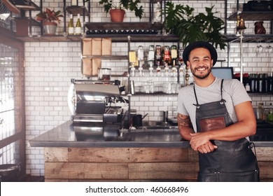 Portrait of young man standing at the counter in his cafe. Coffee shop working in apron and hat smiling at camera.