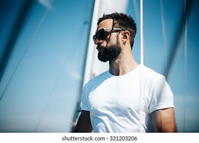 Portrait of young man standing on a yacht and looking at the horizon.