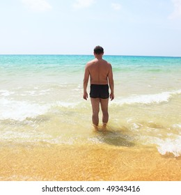 Portrait of a young man standing in the sea