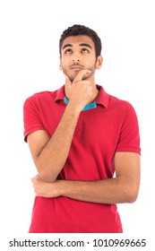 a portrait of a young man standing touching his chin, looking up thinking, isolated on a white background