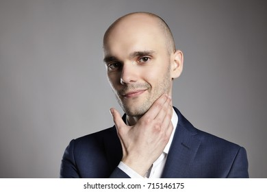 Portrait of a young man stroking his chin. Headshot on gray background.