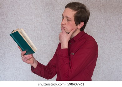 Portrait of a young man student holding a book and reading.