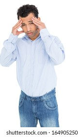 Portrait of a young man suffering from headache against white background