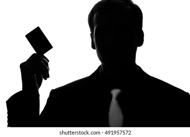 Portrait young man in suit, tie with a rectangular plastic card in hand - front view, silhouette