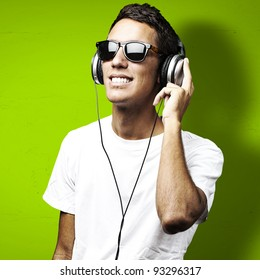 portrait of a young man with sunglasses listening to music on a green background