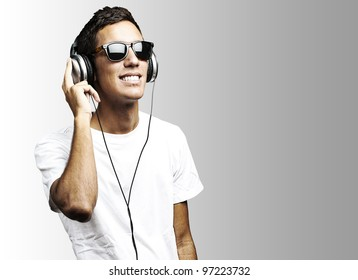 portrait of a young man with sunglasses playing to music on a grey background