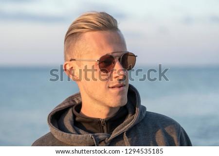 d6eb485f839e Portrait of a young man in sunglasses resting near the sea on the beach,  autumn