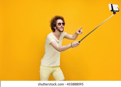 Portrait of young man in sunglasses taking selfie using monopad.Studio shot.Yellow background.Isolate.