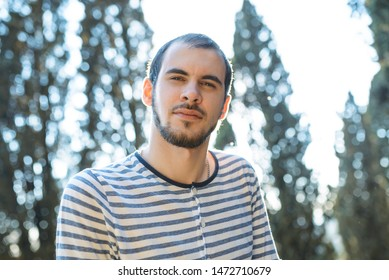 portrait of young man in sunlight at park