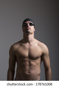 Portrait of a young man with swimming goggles on gray background
