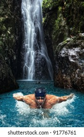 portrait of young man swimming in tropical waterfall