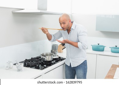Portrait of a young man tasting food while preparing in the kitchen at home