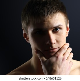 Portrait of young man thinking, black background