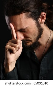 Portrait of young man touching his forehead with index finger