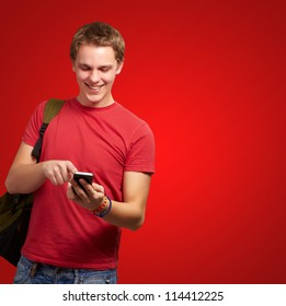 portrait of young man touching mobile screen over red background