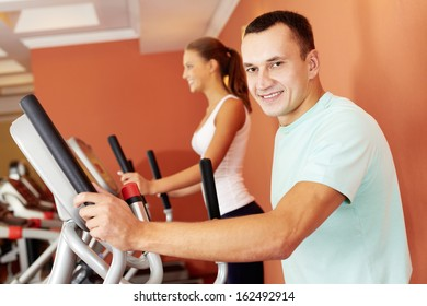 Portrait of young man training on special sport equipment in gym and looking at camera