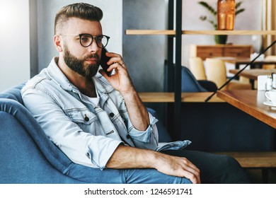 Portrait of young man in trendy glasses sitting in cafe and talking on cell phone. Young male entrepreneur has telephone conversations. Freelancer works remotely. Social communication.