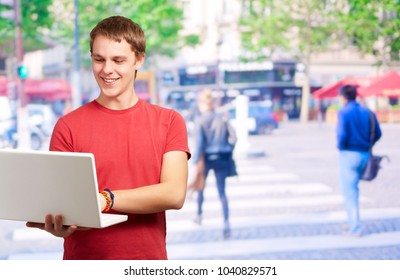 Portrait Of A Young Man Using Laptop, Outdoors