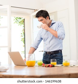 Portrait Of Young Man Using Laptop While Having Breakfast