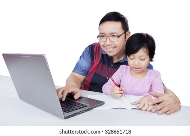 Portrait of young man using laptop computer while helps his child doing school assignment